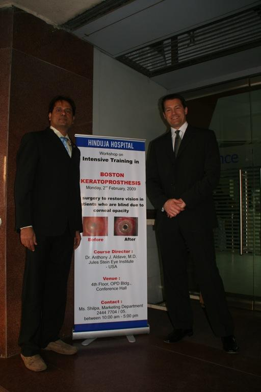 Mr. Chandrashekhar Chawan and Dr. Aldave standing next to an announcement of the training course on Boston keratoprosthesis surgery at Hinduja Hospital.