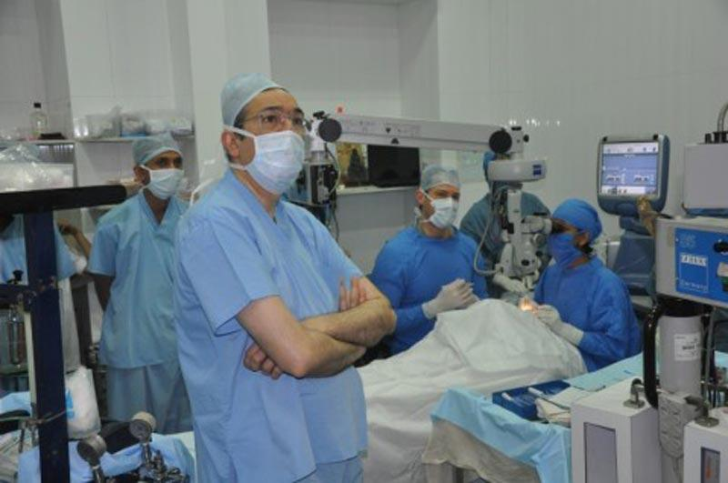 Drs. Aldave and Kothari operate while Dr. Maskati watches the surgery on a monitor at Bombay City Eye Hospital